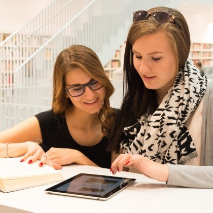 Two attractive female students are stuyding at the public library using a digital tablet and books